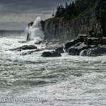 Otter cliffs hit by a wave under a dramatic sky. Acadia National Park.