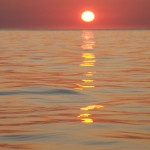 Close to the surface of calm seas with the orange ball of the setting sun on the horizon
