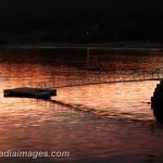 Dock in the reflections of the setting sun.  Acadia National Park, Maine