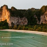 Longtail boats leaving Railay west, the cliffs surrounding Tonsai Beach catch the glow of the setting sun. Thailand