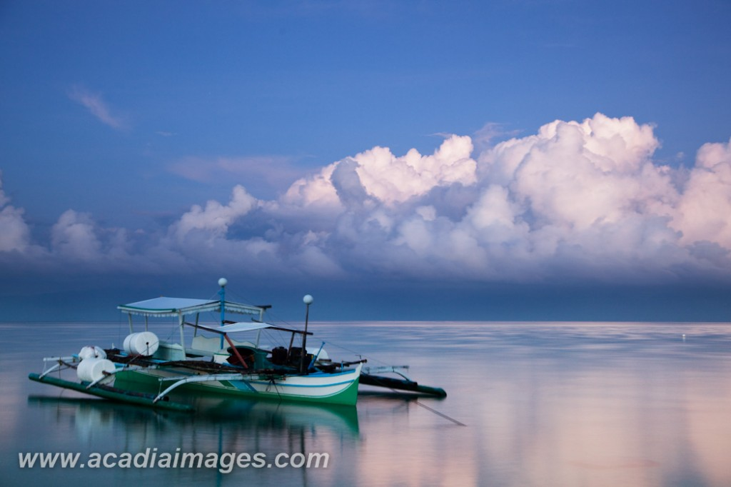 Calm seas in Moalboal, Philippines where a bangka floats, waiting for the fisherman to wake.
