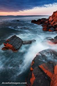 Orange glow of the sun strikes the rocks of the rugged coastline
