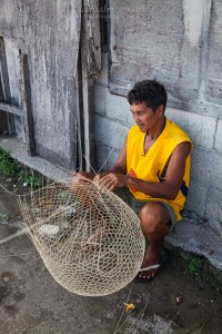 Hand weaving a fish trap out of bamboo.